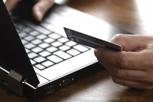 Person with credit card using a computer for internet shopping